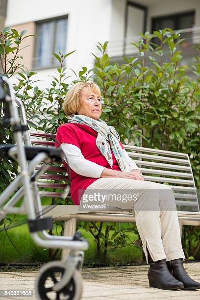 Senior woman with wheeled walker sitting on a bench