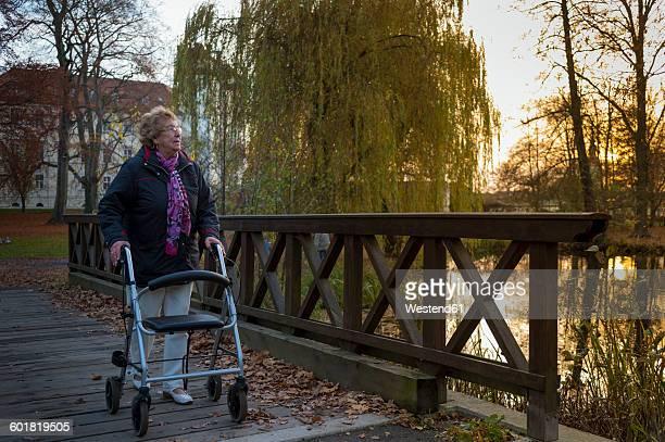 Senior woman with wheeled walker walking on footbridge in the evening