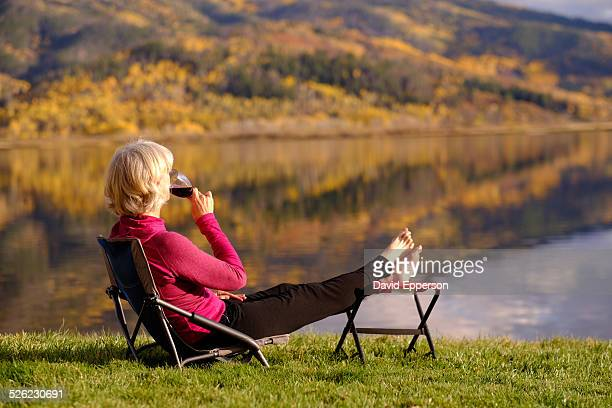 Senior woman with wine glass by alpine lake