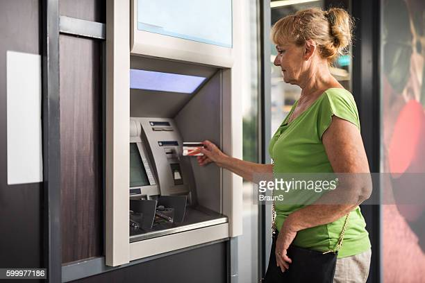 Senior woman withdrawing money from a cash machine.