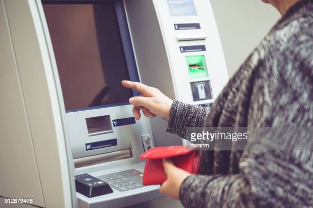 senior woman withdrawing money from atm - atm stock pictures, royalty-free photos & images