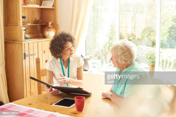 senior woman witrh advisor - house call stock pictures, royalty-free photos & images