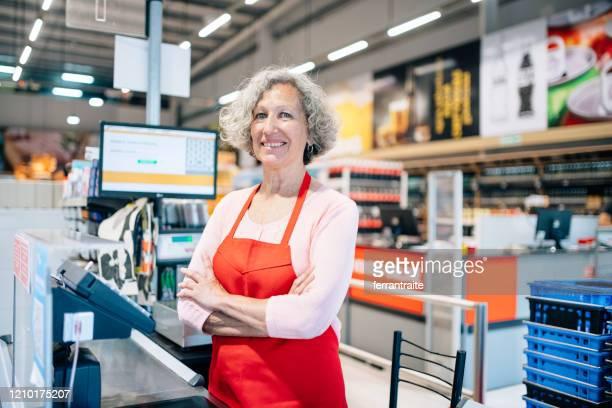 seniorin arbeitet als kassiererin im supermarkt - kassierer stock-fotos und bilder