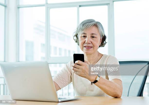senior woman working at home with laptop and cell phone - mourning stock pictures, royalty-free photos & images