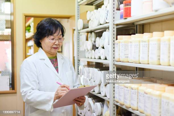 senior woman working in a chinese medicine office - saitama prefecture stock pictures, royalty-free photos & images