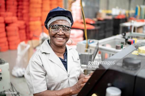 mujer mayor trabajando en un retrato de fábrica - equidad de genero fotografías e imágenes de stock