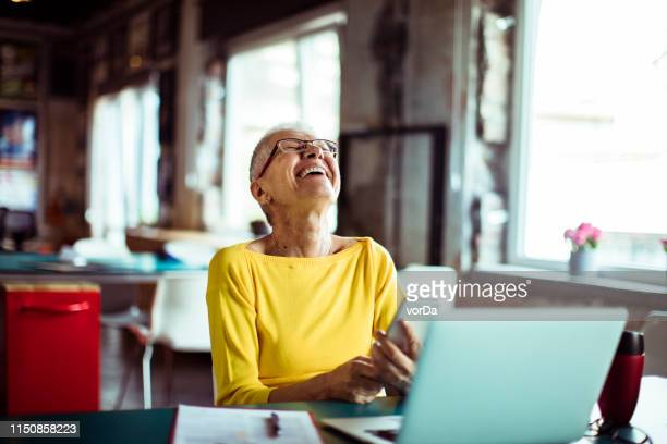 senior woman working in a office - disruptagingcollection stock photos and pictures