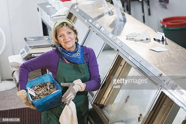 Senior woman working in fish market