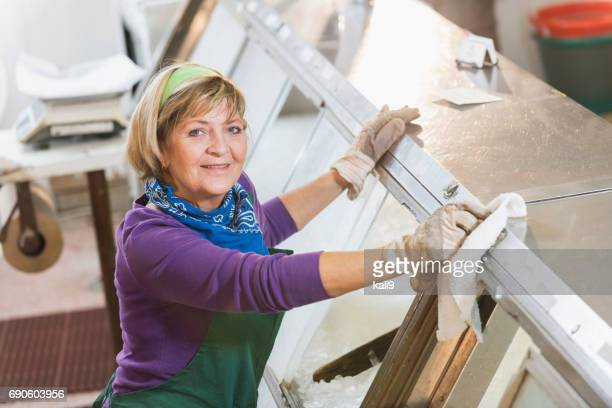 senior woman working in fish market - commercial cleaning stock photos and pictures