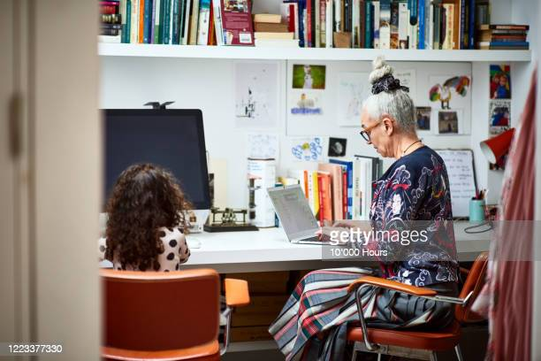 senior woman working in home office with girl - working stock pictures, royalty-free photos & images