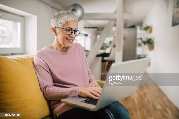 senior woman working on a laptop - online dating stock pictures, royalty-free photos & images