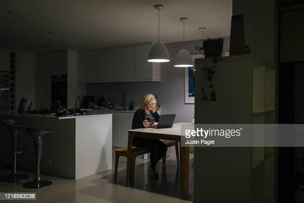 senior woman working on laptop late at night - inquadratura fissa foto e immagini stock