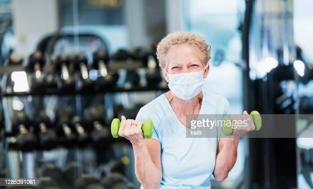senior woman working out at the gym, wearing face mask - practicing stock pictures, royalty-free photos & images