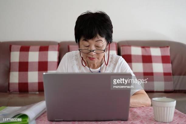 senior vrouw werken met laptop - alleen één seniore vrouw stockfoto's en -beelden