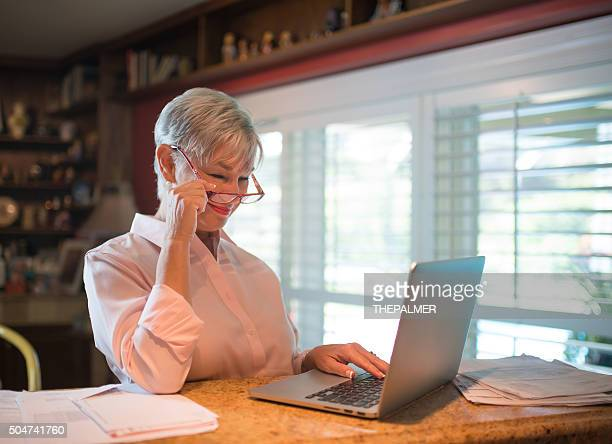 senior woman working with laptop - grandma invoice stock pictures, royalty-free photos & images