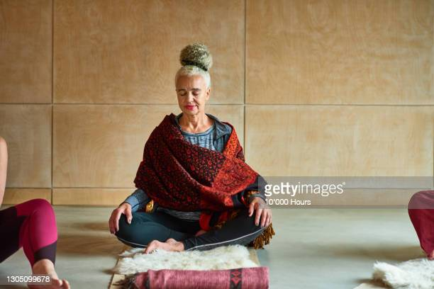 senior woman wrapped in blanket meditating - one senior woman only stock pictures, royalty-free photos & images