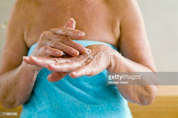 Senior woman wrapped in towel, applying lotion in hands, mid section, close-up