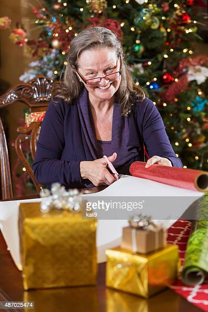 Senior woman wrapping Christmas presents by tree