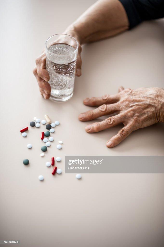 Senior Woman Wrinkled Hands Choosing Medicine To Take : Stock Photo