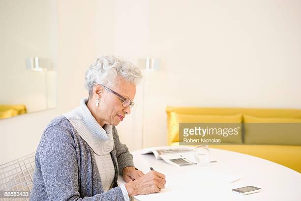 Senior woman writing at home