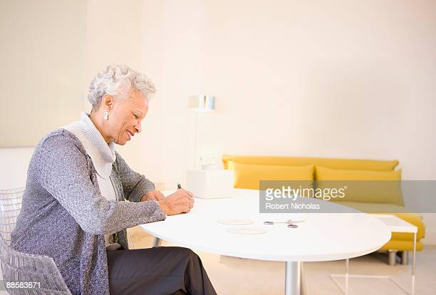 senior woman writing at home - correspondence stock pictures, royalty-free photos & images