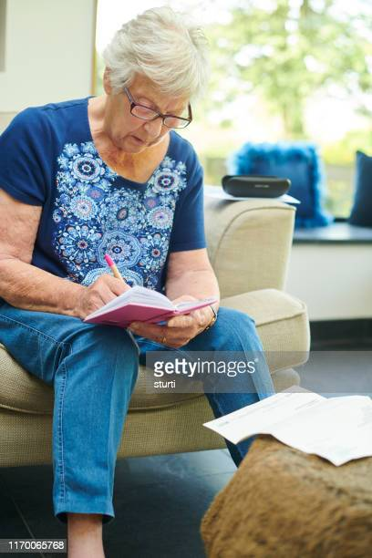 senior woman writing in her diary - correspondence stock pictures, royalty-free photos & images