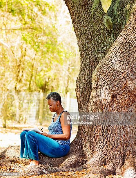 Senior woman writing outdoors