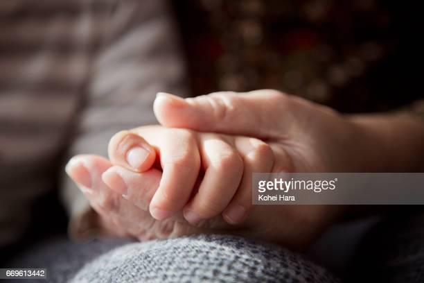 a senior woman's hand holding a boy's hand - zärtlich stock-fotos und bilder