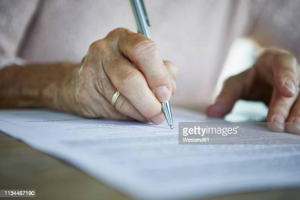 senior woman's hand signing a document, close-up - ondertekenen schrijven stockfoto's en -beelden