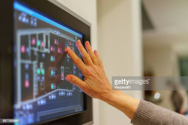 Senior womans hand touching display panel of domestic technology