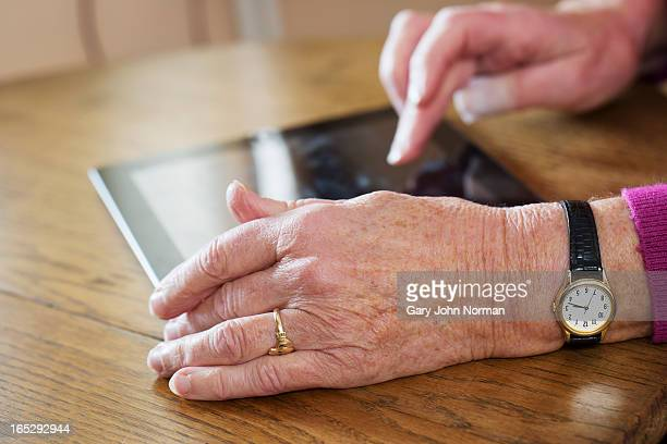 senior woman's hands using digital tablet - norman elder stock photos and pictures