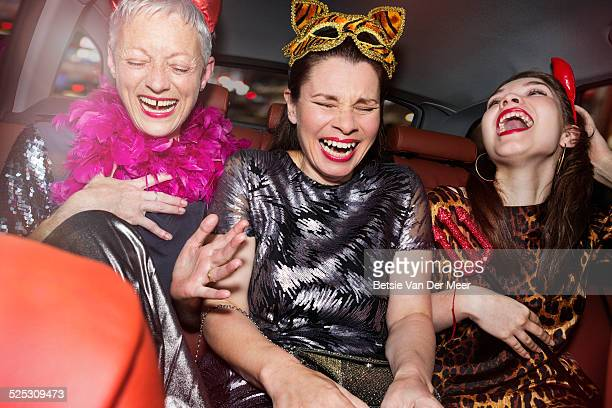 senior women and daughter laughing in car.
