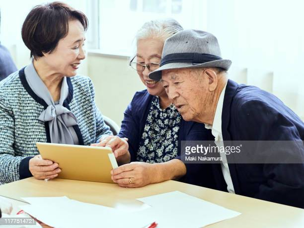 Senior women and men talking happily while looking at iPad
