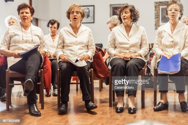 senior women at choir practice - choir stock pictures, royalty-free photos & images