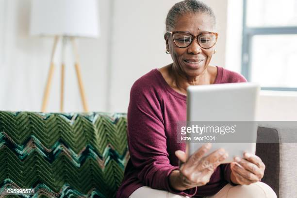 senior women at home using tablet - using digital tablet stock pictures, royalty-free photos & images