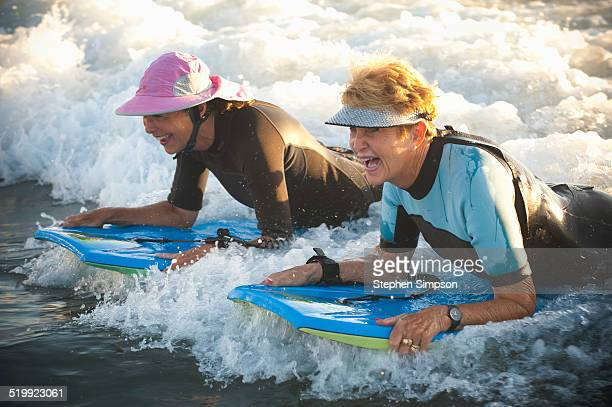 senior women at the beach with body boards