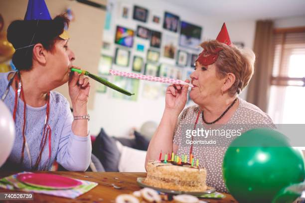 senior women blowing party favor at each other - birthday balloons stock photos and pictures