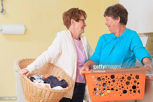 Senior women carrying baskets and talking in a laundry room