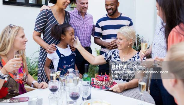 """senior women celebrating birthday with multi generation family at patio table - """"compassionate eye"""" stock pictures, royalty-free photos & images"""