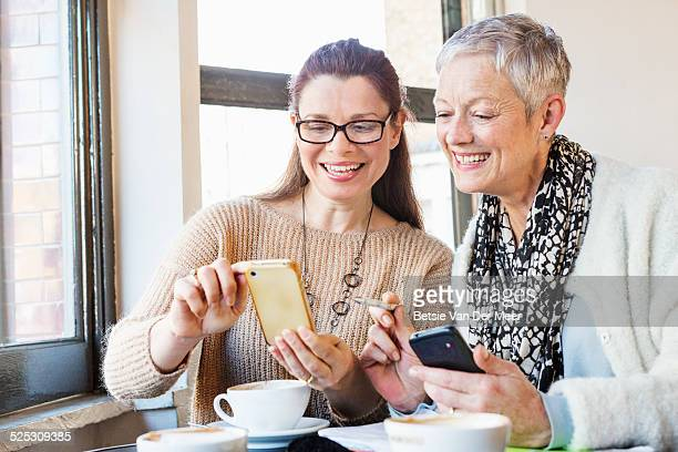 Senior women comparing diaries in cafe.