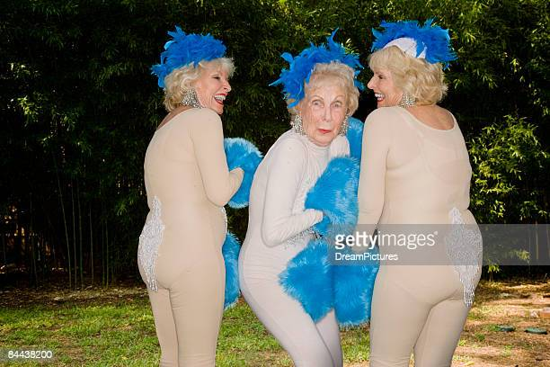 Senior women dancing in nude outfits.