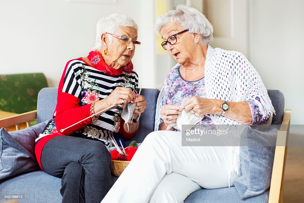 Senior women discussing while knitting at nursing home : Stockfoto