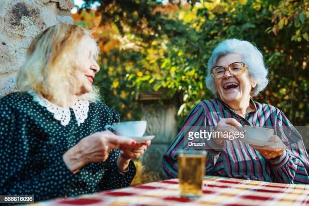 femmes âgées de boire du café et de rire - mamie humour photos et images de collection