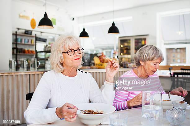 Senior women eating food on table at restaurant