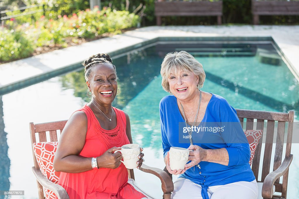 Senior women enjoying cup of coffee by swimming pool : Stock Photo