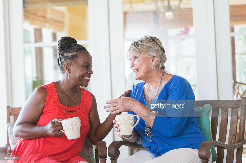 Senior women enjoying cup of coffee together, talking : Stock Photo