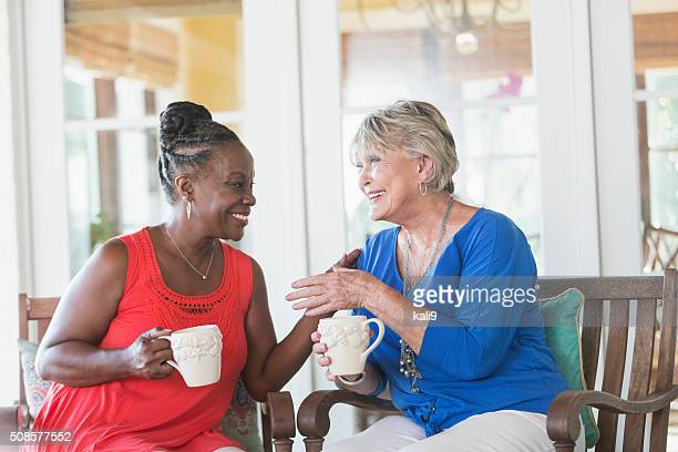 Senior women enjoying cup of coffee together, talking