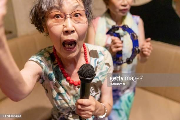 senior women enjoying karaoke - singer stock pictures, royalty-free photos & images