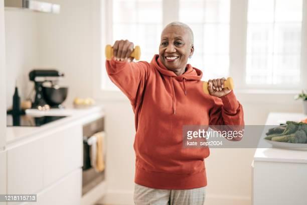 seniorinnen trainieren zu hause - fitnesstraining stock-fotos und bilder