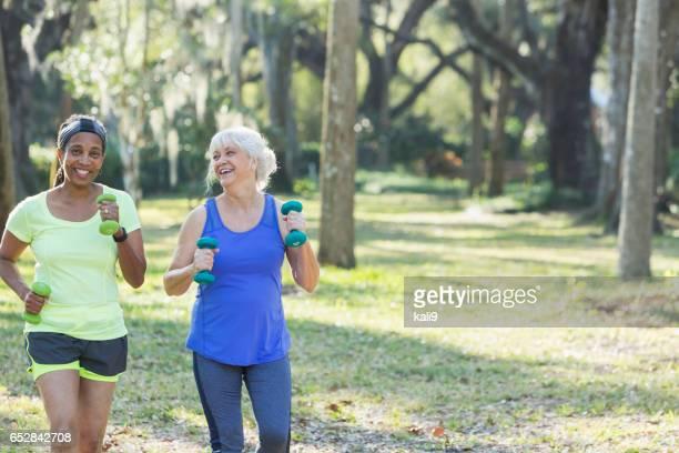 Senior femenino haciendo ejercicio en el parque, correr con pesas de mano